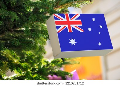 Australian flag printed on a Christmas gift box. Printed present box decorations on a Xmas tree branch. Christmas shopping in Australia, sale and deals concept.