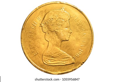 Australian golden chocolate coin of 1 dollar of Australia, AUD currency, close up of the head side of Queen Elizabeth II. Isolated on white studio background.