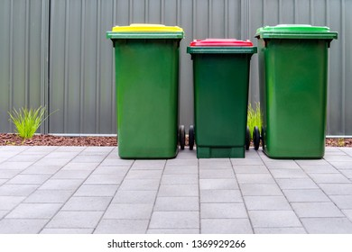 Australian home outdoor bins set provided by local council placed on backyard of suburban house