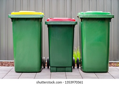 Australian home waste wheelie bins set provided by local council installed on backyard of suburban house