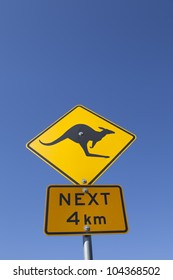An Australian kangaroo warning road sign against a vibrant blue sky.
