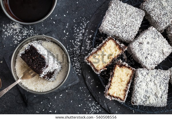 australian lamington cakes with chocolate and coconut. dark background. top view