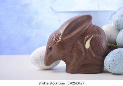 Australian milk chocolate Bilby Easter egg with eggs in nest against a blue and white background, with copy space.