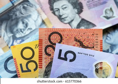 Australian money background.  Focus on foreground, blurred faces beneath.
