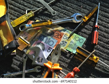 Australian money and handyman's tools on gray-black work mat outdoors in direct sunlight