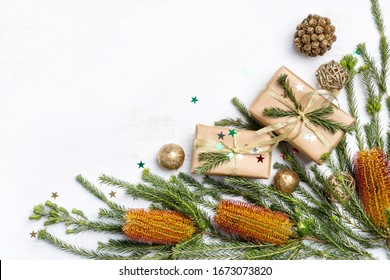 Australian native plant Banksia frames the Christmas inspired background. Gifts, gold ribbon, glitter, cream pine cones and other Christmas decorations on a rustic white background. Space for copy.
