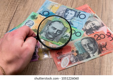 Australian notes under a magnifying glass in hand