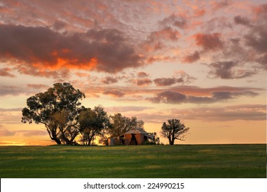 Australian outback sunset.  Old farm house, crumbling walls and verandah w sits abandoned on a hill at sunset. The last sun rays stretching across the landscape painting the grass in dappled light