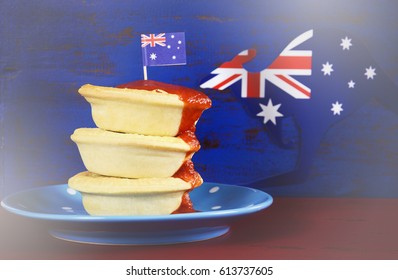 Australian party food with iconic meat pies and tomato sauce on dark red and blue vintage rustic recycled wood background, with applied retro vintage style filters.