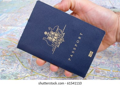 australian passport being holdr on top of paris map