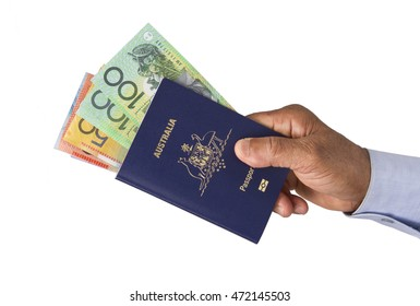 Australian Passport with dollars in hand isolated in white background.