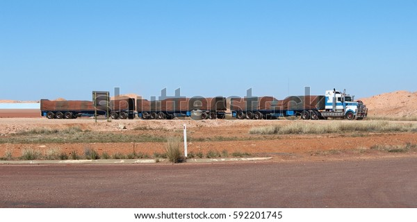 Australian road train with green and brown striped tarpaulin in full-length.