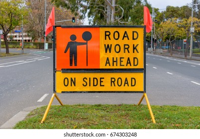 """Australian """"Road Work Ahead""""  """"on Side Road""""road sign with orange flags"""