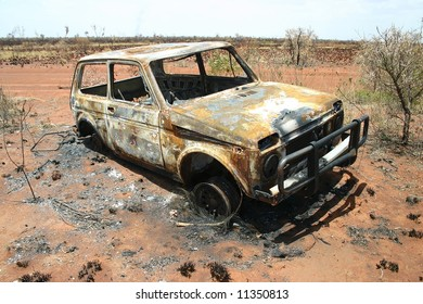 Australian rural road with an obsolete burned car on roadside. Tanami road, Northern Territory. Australia