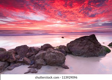 australian seascape at sunrise with rich in red color cloud formation