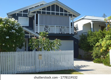 Australian style, old fashioned timber frame home with white front fence and garden