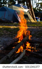 Australian summer time camp fire with blurred tents in background