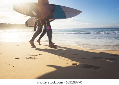 Australian surfers walking along Bondi Beach in the early morning for a surf