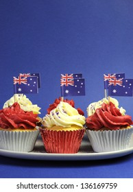 Australian theme red, white and blue cupcakes with national flag for Australia Day, Anzac Day or national holiday against a blue background. Vertical with copy space.
