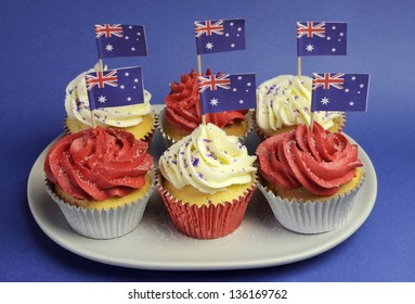 Australian theme red, white and blue cupcakes with national flag for Australia Day, Anzac Day or national holiday against a blue background. Close-up.