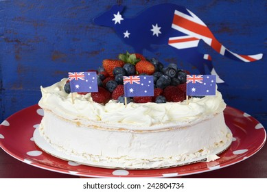 Australian traditional dessert, Pavlova, with whipped cream and strawberries, blueberries and raspberries in red white and blue theme with Australian flag.