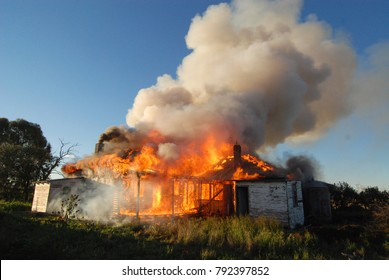Australian weatherboard house on fire with a cloud of smoke billowing from the top.