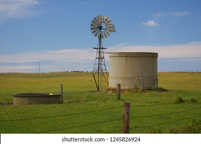 An Australian windmill erected beside a water tank and water trough in a green paddock.