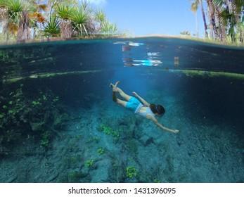 Australian woman diving in Bitter Springs near Mataranka in the Northern Territory, Australia.