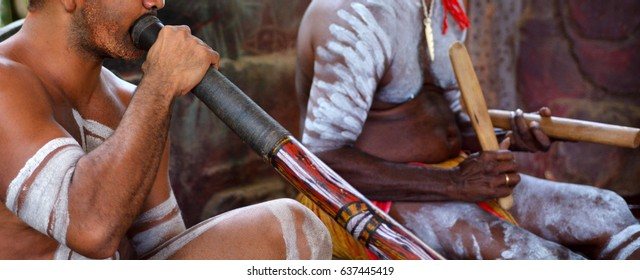 Australians Aboriginal men playing Aboriginal music on didgeridoo and wooden sticks in a culture ceremony festival event in the Far North Queensland, Australia.