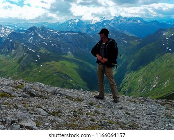 Austria. Alps. Weißeck. Point of observation. A hiker is looking into the distance. A hiker with a backpack looks at the rocks.