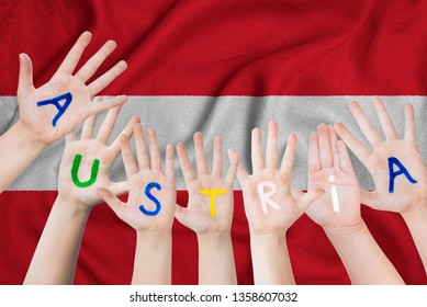 Austria inscription on the children's hands against the background of a waving flag of the Austria.