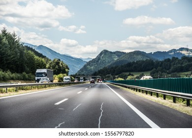 Austria - July, 2019: Autobahn or highway with a bridge in the mountains with clear marking surrounded by vibrant green trees under blue sky.