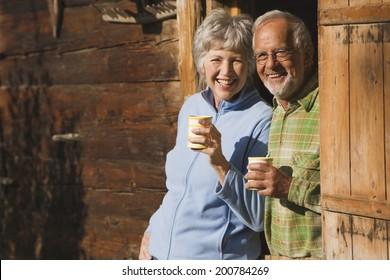 Austria, Karwendel, Senior couple leaning on log cabin's entrance holding mugs