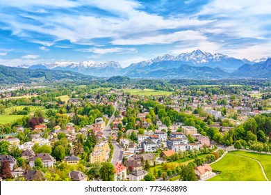 Austria, Salzburg city, Europe. Spring skyline of Salzburg at the background of high mountains Alps, view from above. City scenery in green valley among trees. Harmonic existence of urban and nature.