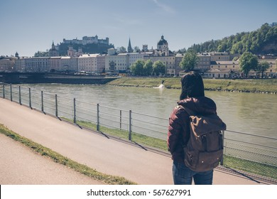 Austria. Salzburg. Girl tourist standing on the banks of the Salzach river and looking at the old town and fortress Hohensalzburg