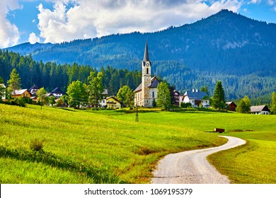 Austria. Traditional church with chapel in village among picturesque landscapes in austrian Alps mountains. Summer green lawns and fields. Knolls covered with forests and trees. Blue sky with clouds.