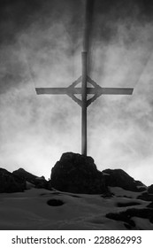 Austria, tyrolean alps, wooden cross with backlight and a dramatic sky