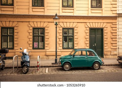 Austria, Vienna, 20 August 2010: Fiat 500 and a vintage moped are parked on a street in the city center.