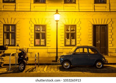 Austria, Vienna, 20 August 2010: Fiat 500 and a vintage moped are parked on a street in the city center at night.
