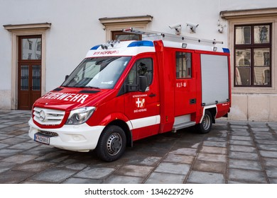 Austria, Vienna, Hofburg Palace: Side view of red white Daimler Mercedes Benz Sprinter fire engine truck in the city center of the Austrian capital - concept public service help. February 01, 2019