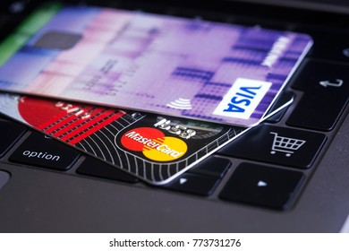 AUSTRIA, WIENNA - DEC 06, 2017: Close up of credit cards on a laptop keyboard with shopping cart symbol. Concept image for online shopping, data security, e-commerce. Selective focus.