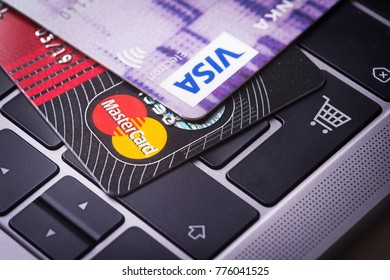 AUSTRIA, WIENNA - DEC 06, 2017: Close up of credit cards on a laptop keyboard with shopping cart symbol.. Concept image for online shopping, data security, e-commerce. Selective focus.