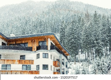 Austrian alpine village scenic landscape with small chalet and pine forest trees and snow covered mountains on background during snowfall. Cold frosty snowstorm weather