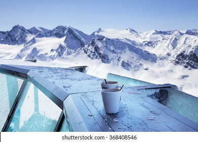 The austrian Alps mountain panorama view from the restaurant terrace with the coffee cups in front