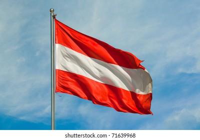 austrian flag on a pole over beautiful sky