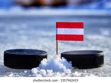 Austrian flag on toothpick between two hockey pucks. Winter classic. Flag on frozen pond on unkempt ice. Traditional pucks for international matches.
