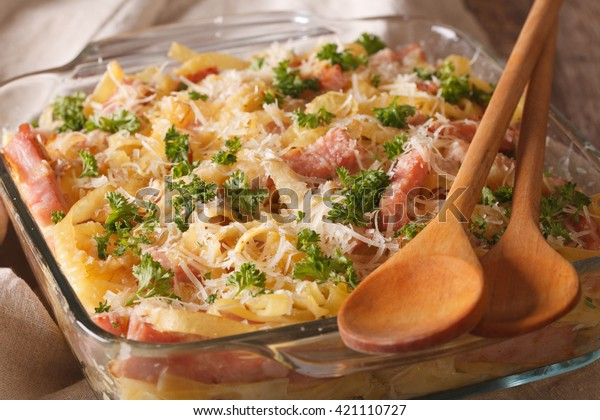Austrian noodles with ham and parmesan close-up in a glass baking dish on the table. horizontal