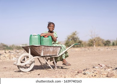 Authentic African ethnic Young Girl Collecting fresh Water as a drought symbol