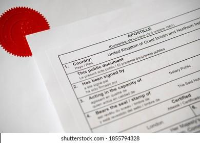 """Ursprüngliche Urkunde der Apostille. Der rote Stempel """"NOTARY PUBLIC"""" auf dem offiziellen Dokument auf unscharfem Hintergrund. Echte Dokumente."""