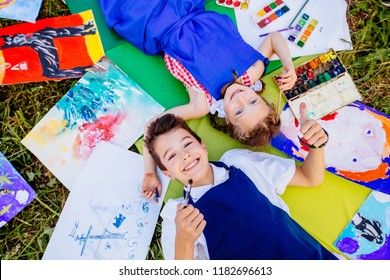 Authentic artist children in blue aprons girl and boy paints tickle each other by paint brushes, lying in creative chaos palette watercolor paints, brush, drawings.Painting outdoor. Top view